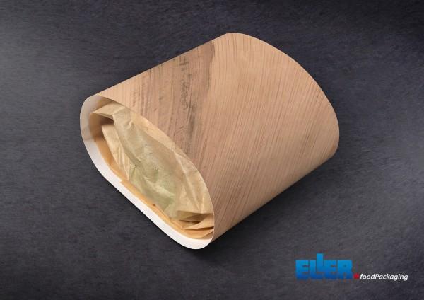 Quibbon Burger Verpackung aus braunem Papier liegt auf dunklem Tisch