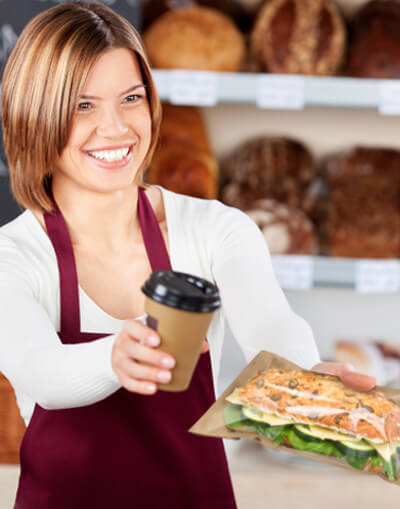 Bakery saleswoman presents packed snack and coffee mug