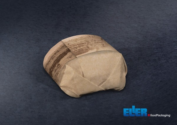 Verpackter Hamburger in braunem Einwickelpapier mit braun bedruckter Banderole iin Palmblatt Optik