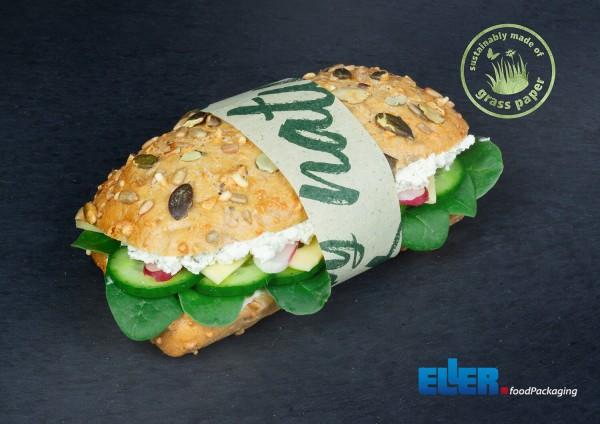 Umweltfreundliche Banderole aus Graspapier hält einen Sandwich zusammen.